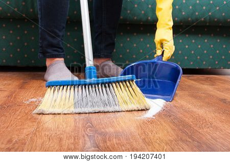 Closeup of maid woman sweeping floor with broom and dustpan at home stock photo