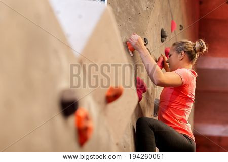 fitness, extreme sport, bouldering, people and healthy lifestyle concept - young woman exercising at indoor climbing gym stock photo