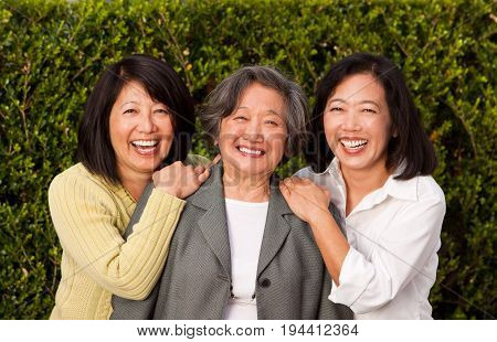 Happy mature Asian mother and her adult daughters. stock photo