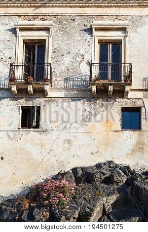 travel to Sicily Italy - old urban house on volcanic rock base in Giardini Naxos town in summer stock photo