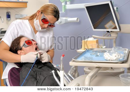 Female dentist whitening teeth with multi purpose laser - a series of DENTAL related images. stock photo