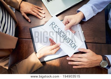 Hand of a businessman hands over a resignation letter on a wooden table to his boss. stock photo