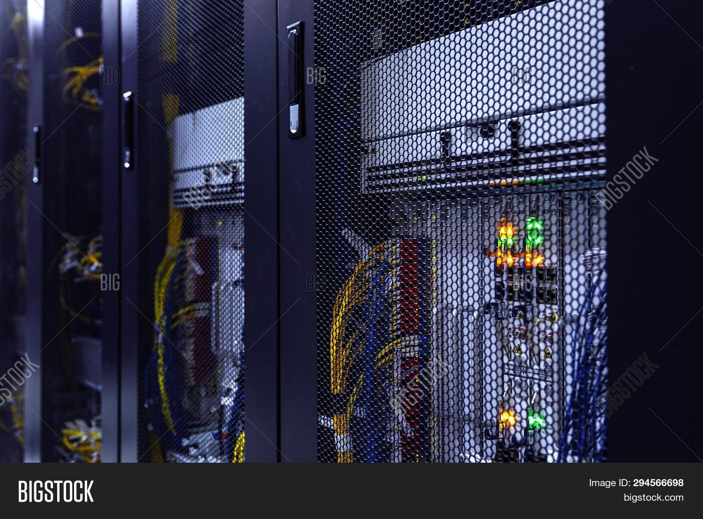 Close up server rack with LED indicator inside under meshed door. Computer server in rack, network and hardware. Inside mainframe.