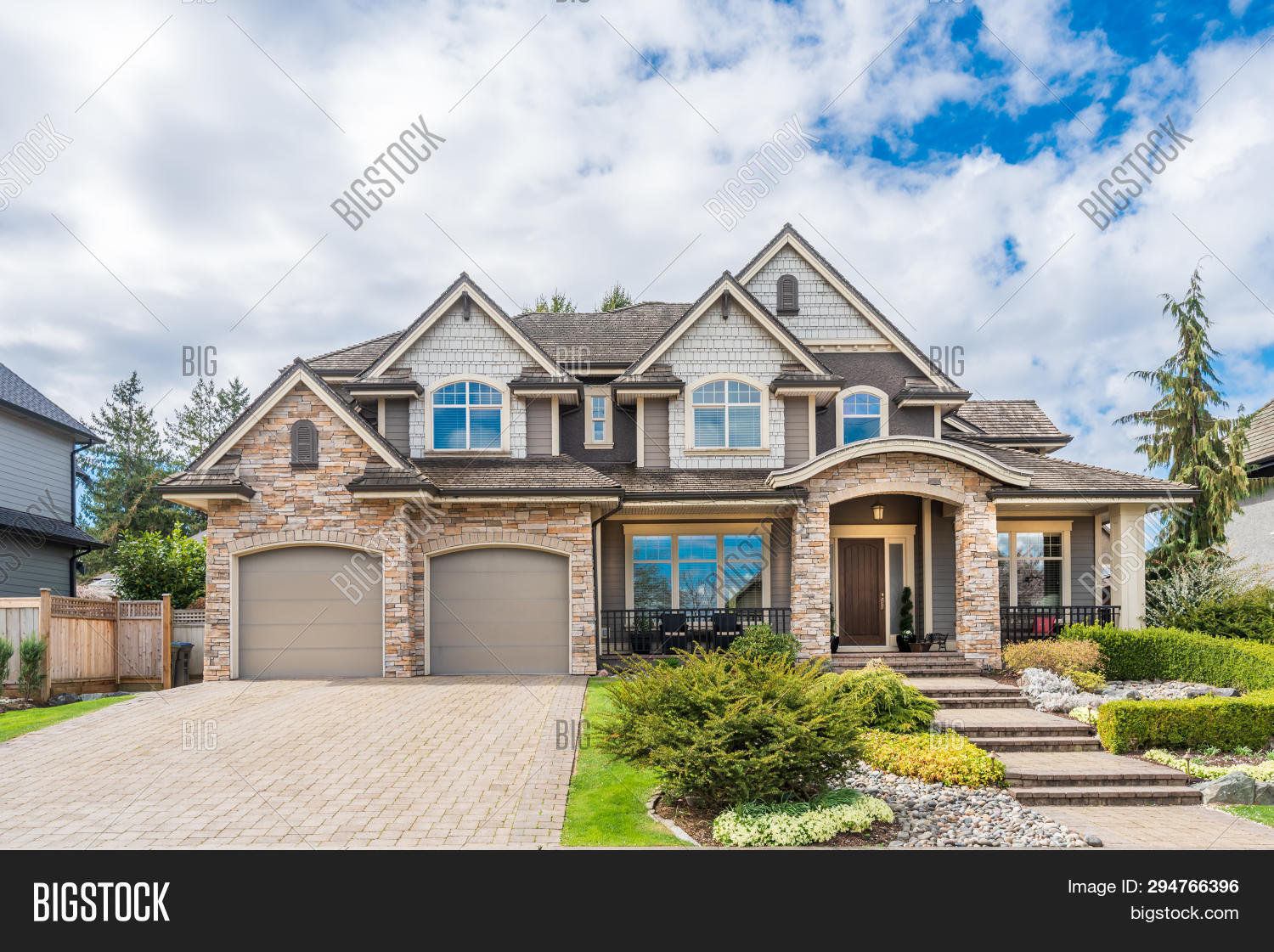 Beautiful exterior of newly built luxury home. Yard with green grass and walkway lead to front entra
