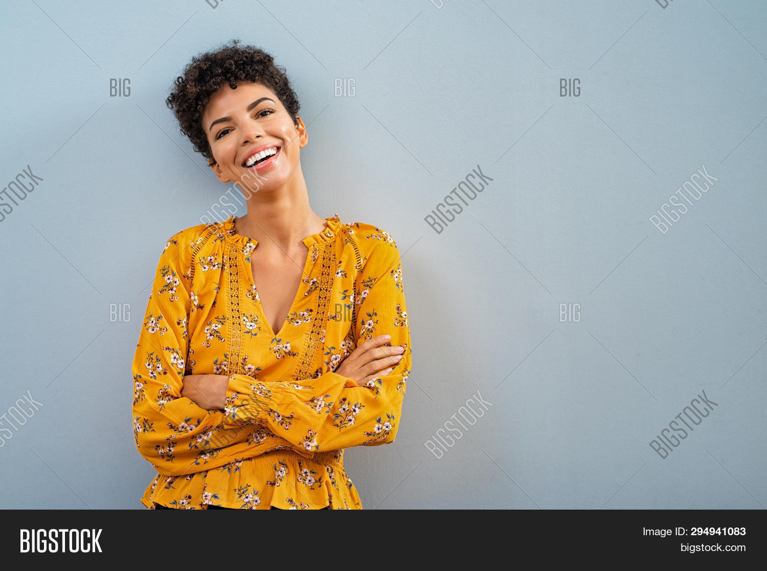 Portrait of beautiful cheerful girl smiling and looking at camera. Happy african woman in casual on