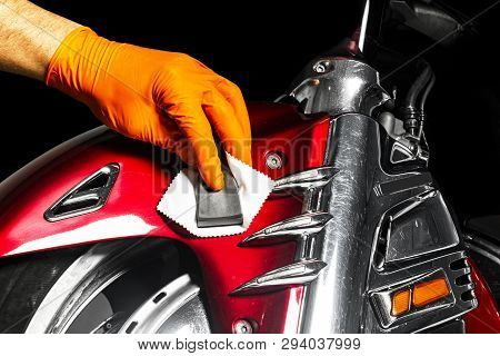 Car polish wax worker hands applying protective tape before polishing. Buffing and polishing motorcycle. Car detailing. Man holds a polisher in the hand and polishes the motorcycle stock photo