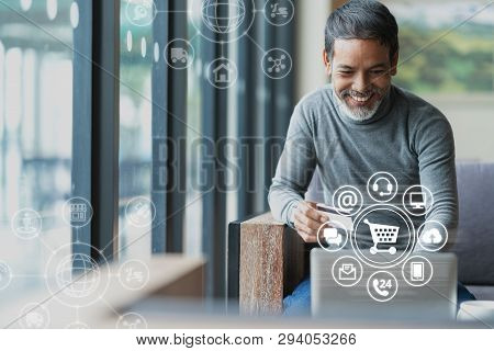 Asian or Hispanic man using Laptop and credit card payment shopping online with icon customer network connection on screen and connecting with omni channel system. Older man satisfied with CRM system stock photo