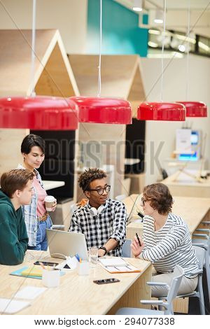 Group Of Content Young Multiethnic Students In Casual Clothing Sitting At Table And Using Laptop Whi