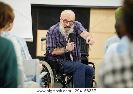 Emotional Confident Motivational Disabled Speaker With Gray Beard Sitting In Wheelchair And Pointing