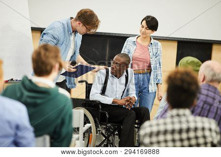 Live Interaction With Disabled Young Scientist: Content Young Man In Glasses Supporting Black Man In