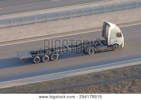 Truck with an empty long trailer without cargo, driving on the highway, top above view stock photo