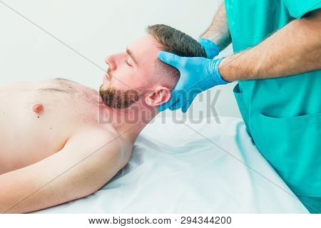 Male patient receiving massage from therapist. A chiropractor stretching his patient's neck in medical office. Neurological physical examination. Osteopathy, chiropractic, physiotherapy. Isolated stock photo