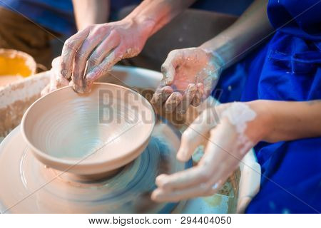 Traditional pottery making, man teacher shows the basics of pottery in art studio. Artist operates hands, which gently creating correctly shaped jug handmade from clay stock photo