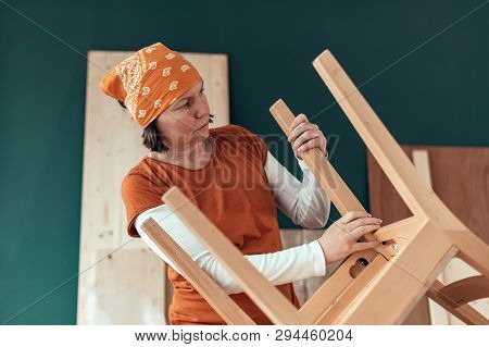 Female carpenter repairing wooden chair seat in small business woodwork workshop stock photo