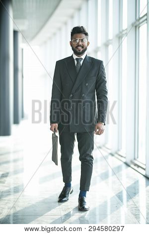 Full length shot of a stylish young businessman wearing a modern suit, who is a high achiever, standing on the top floor of an office building looking out at the view through large windows stock photo