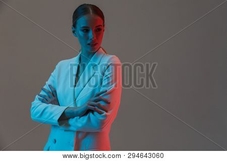 Photo of adorable woman 20s wearing elegant jacket posing at camera and standing under neon lights isolated over gray background stock photo