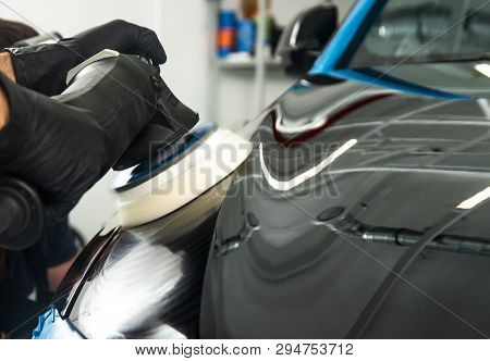 Car polish wax worker hands applying protective tape before polishing. Buffing and polishing car. Car detailing. Man holds a polisher in the hand and polishes the car. Tools for polishing stock photo