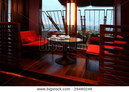 White cup, sugar-bowl and teapot on table, red seats in empty restaurant at evening stock photo
