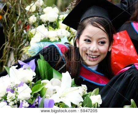 Portrait of a beautiful Asian university graduate in robes. stock photo