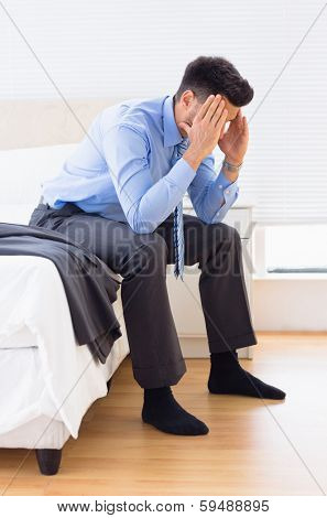 Hungover businessman sitting at edge of bed at home in bedroom stock photo