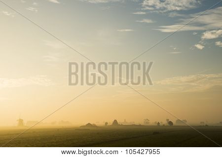 Peaceful sunrise with two wind mills cows fog in Streefkerk Holland. stock photo
