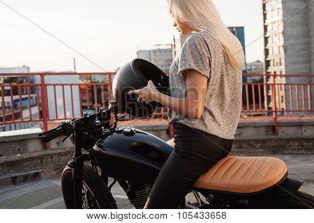 Fashion female biker girl. Young Blonde woman in leather jacket sitting on vintage custom motorbike. Outdoors lifestyle portrait stock photo