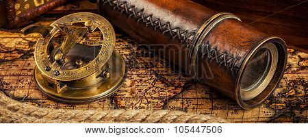 Travel geography navigation concept background - letterbox panorama of old vintage retro compass with sundial, spyglass and rope on ancient world map stock photo