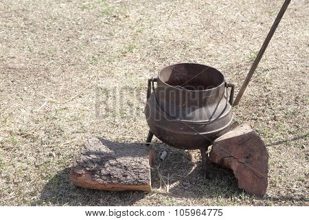 old iron cauldron and wooden logs on a outdoor scene ** Note: Shallow depth of field stock photo