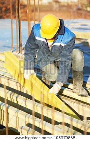construction worker at construction site assembling falsework for concrete pouring stock photo
