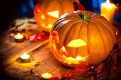 Halloween pumpkin head jack light with blazing candles over wooden foundation. Halloween occasions