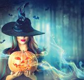Halloween Witch with an enchantment Pumpkin in a dull timberland. Wonderful young lady in witches ca