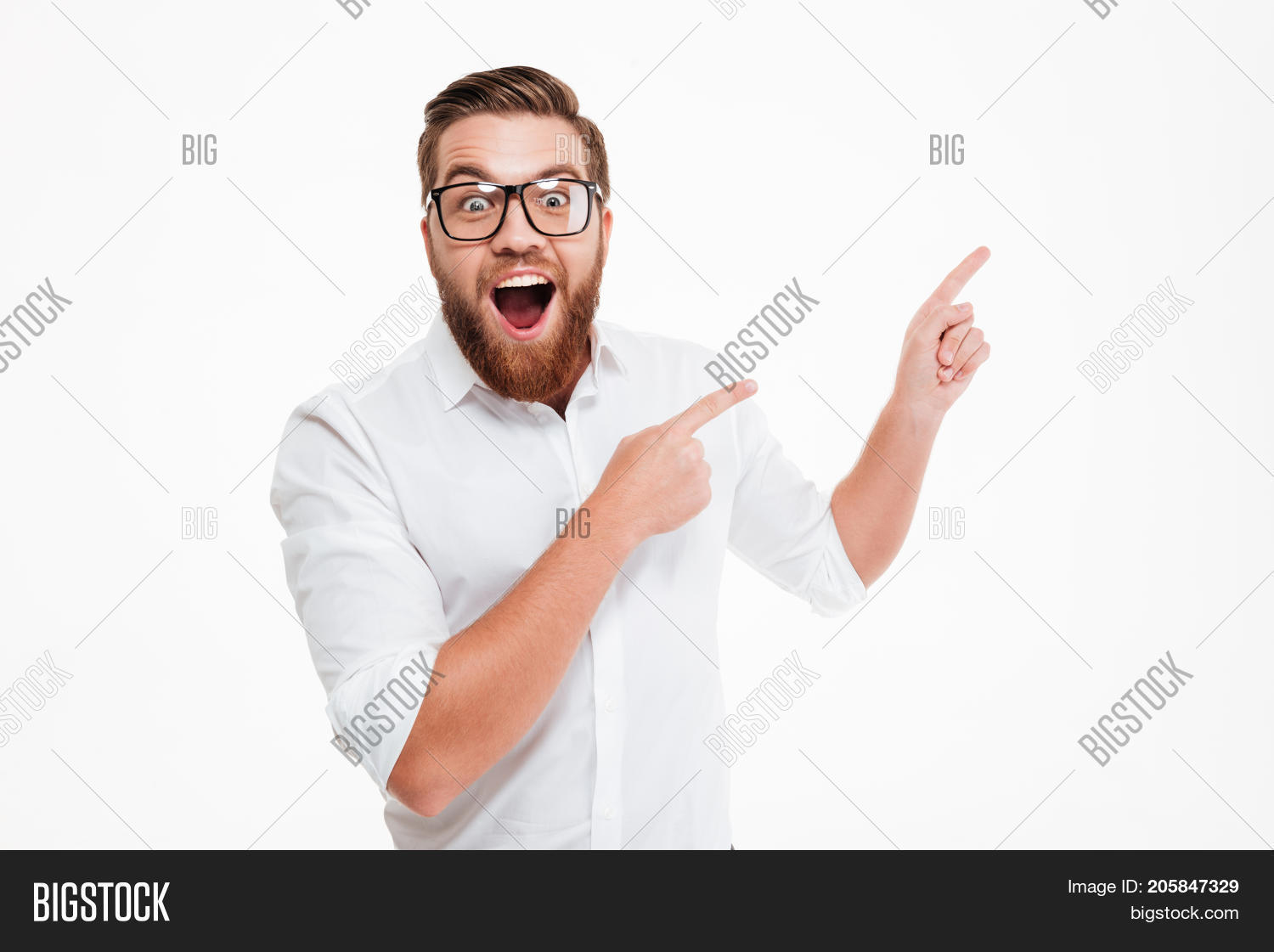 Happy excited bearded man in eyeglasses pointing away at copy space with two fingers isolated over w