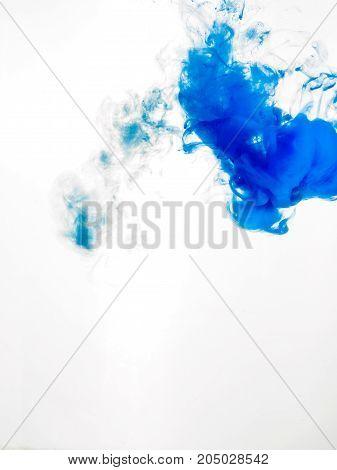 Ink swirl in water isolated on white background. The paint in the water. Soft dissemination a droplets of blue ink in water close-up. Abstract background. Soft focus. stock photo