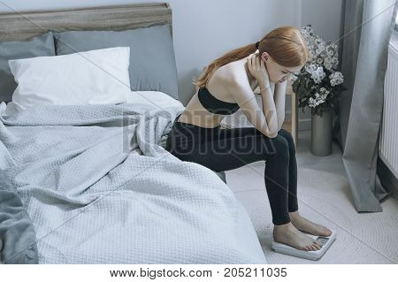 Underweight red hair woman looking at the scale with aversion stock photo