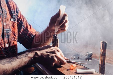 Vaper device repair service. Ecig rapairing process. process of replacing cotton wool cotton pulp in a vape device hands view close stock photo