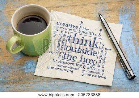 Think outside the box concept - word cloud on a napkin with a cup of coffee