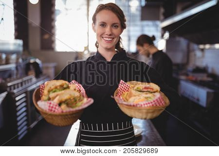Portrait of smiling waitress serving fresh burgers in baskets standing at coffee shop stock photo