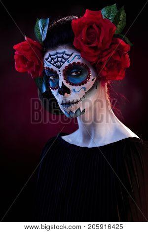 Studio portrait of spooky woman wearing santa muerte mask at halloween, looking at camera.