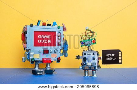 Game over cyber safety concept. Creative design robotic toys on blue ground yellow wall. Monitor computer pixel warning message, small cyborg memory card with text