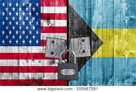 US and Bahamas flag on door with padlock stock photo