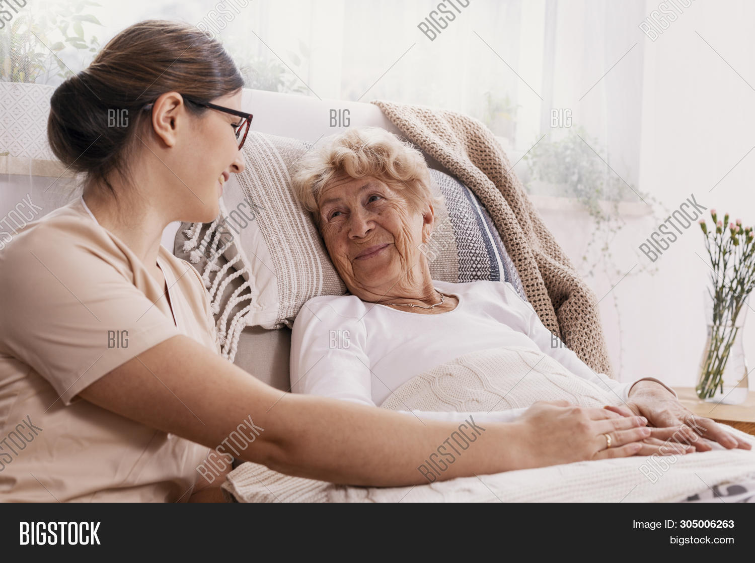 Elderly Woman In Hospital Bed With Social Worker Helping Her