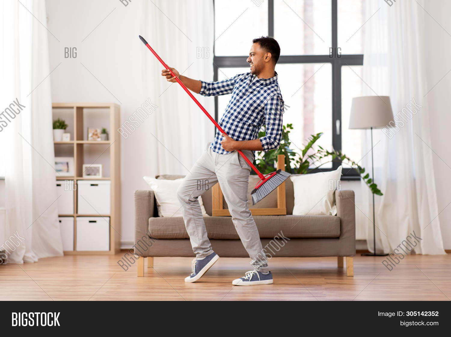 cleaning, housework and housekeeping concept - indian man with broom sweeping floor and having fun a