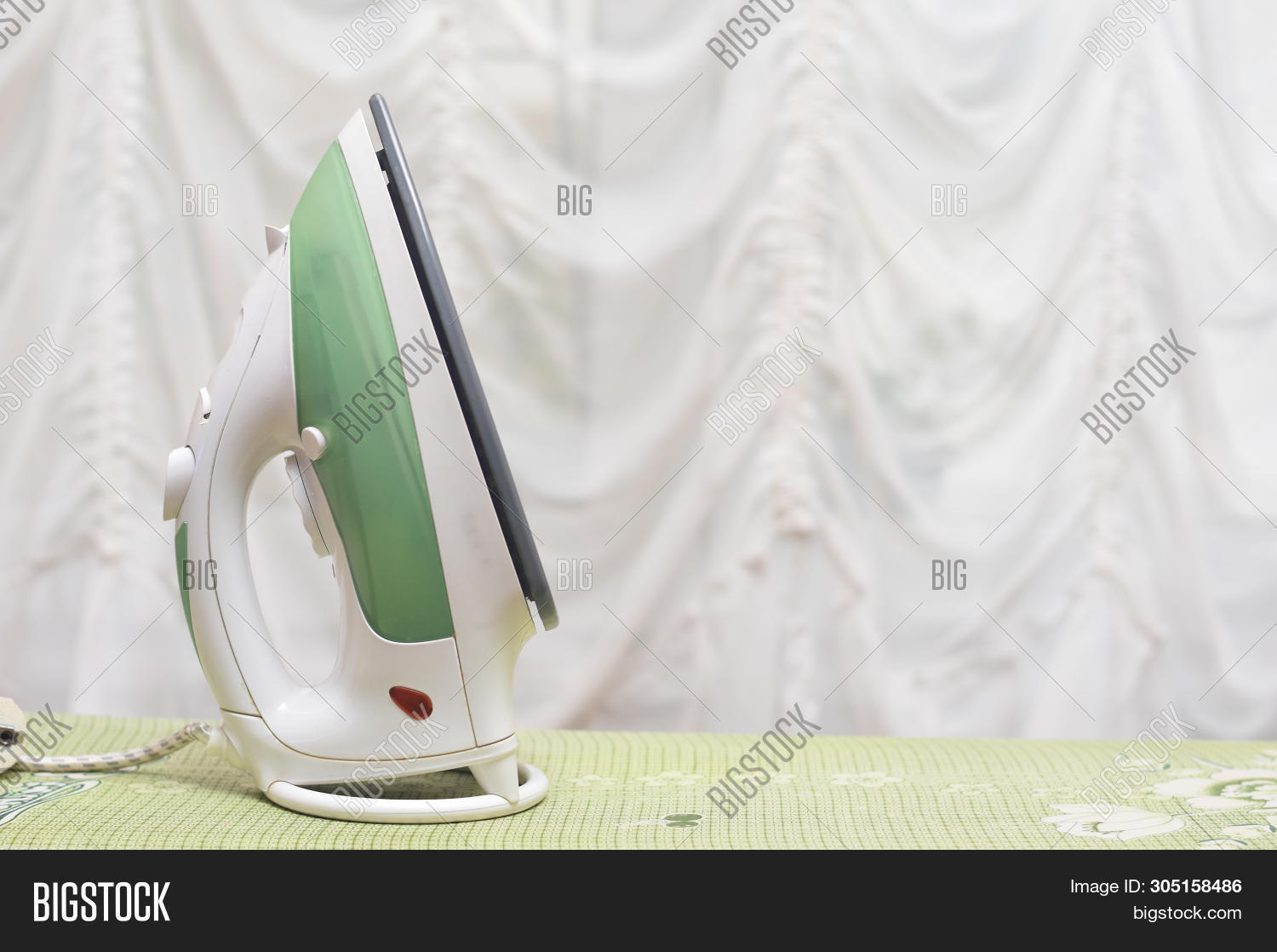 Iron And Clothes On Ironing Board. Concept Of Ironing