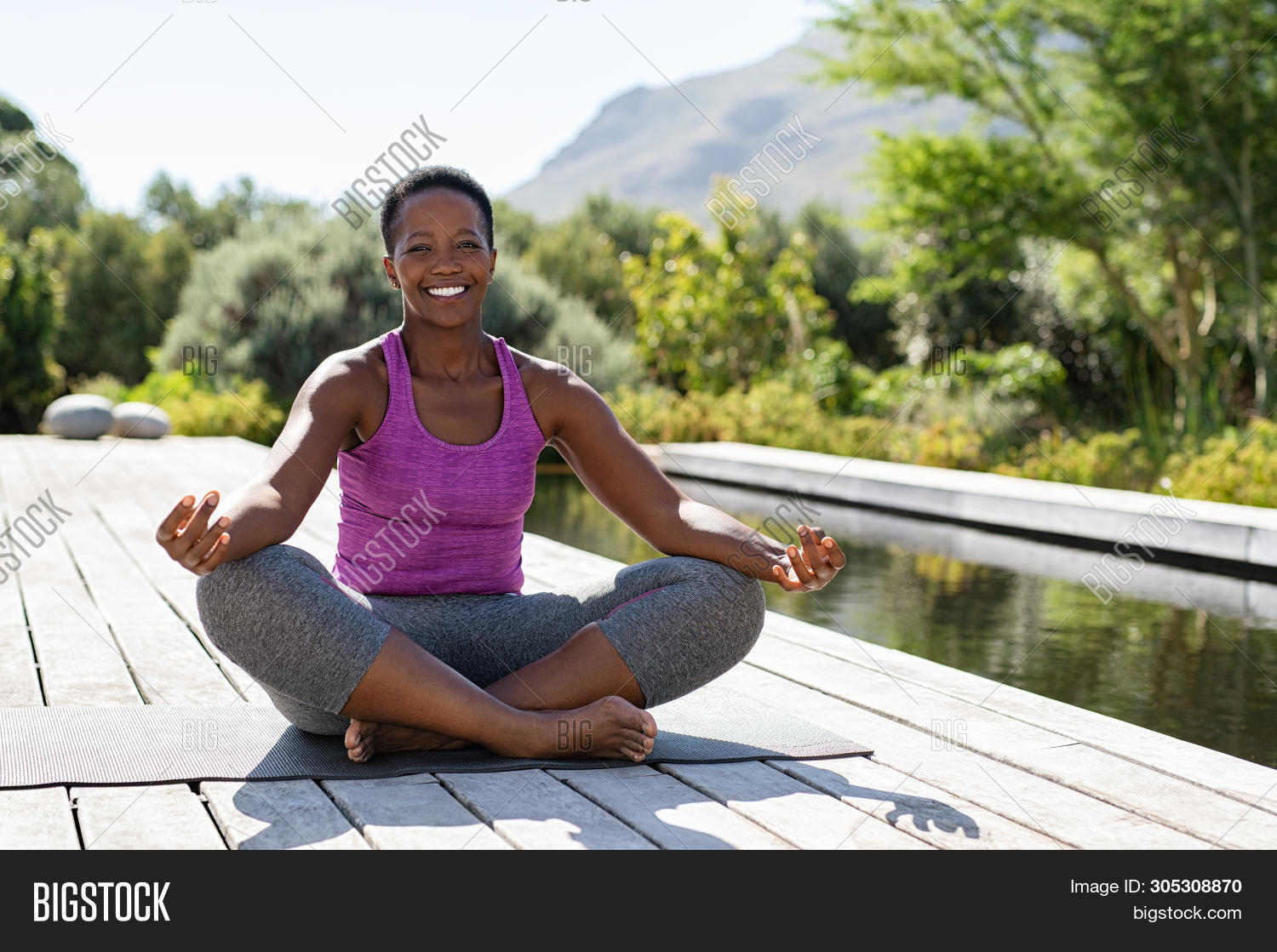 Portrait of smiling woman in lotus position near swimming pool looking at camera. Healthy black matu