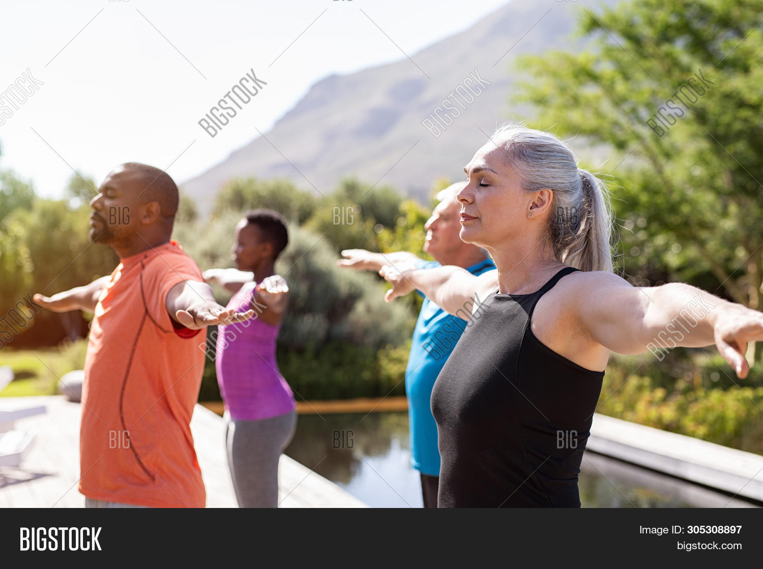 Group of senior people with closed eyes stretching arms outdoor. Mature yoga class doing breathing e