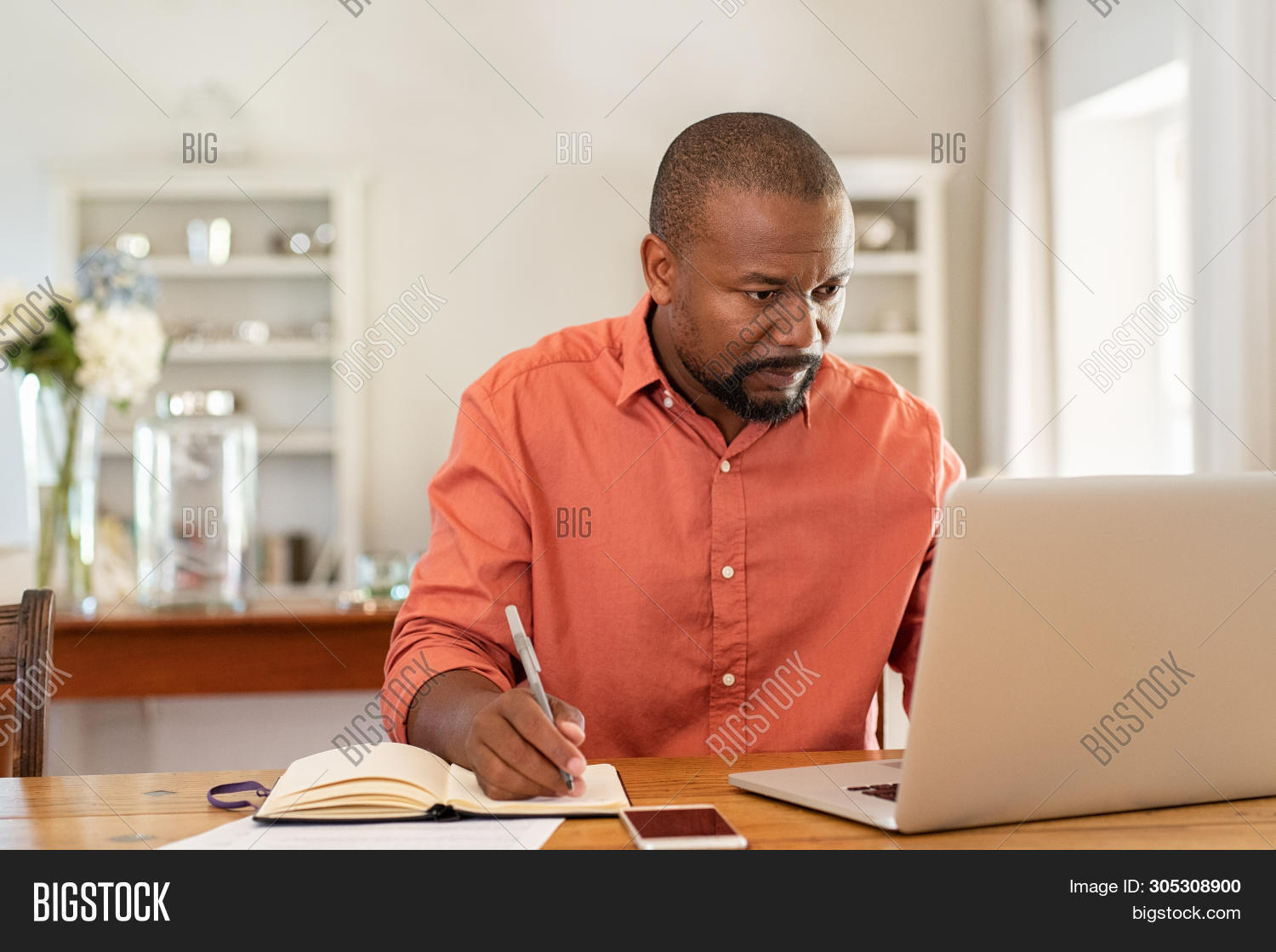 accounting,african,african american,african man,american,bill,black,business,businessman,casual business,communication,computer,counting,finance,finances,financial,home,home banking,home finance,indoor,internet,job,laptop,learning,managing money,mature,mid adult man,middle aged man,notebook,online,people,planning,problem,problem solving,problems,risk,serious,serious man,sitting,studying,table,taking notes,technology,using computer,using laptop,wireless,work,working at computer,working at home,writing