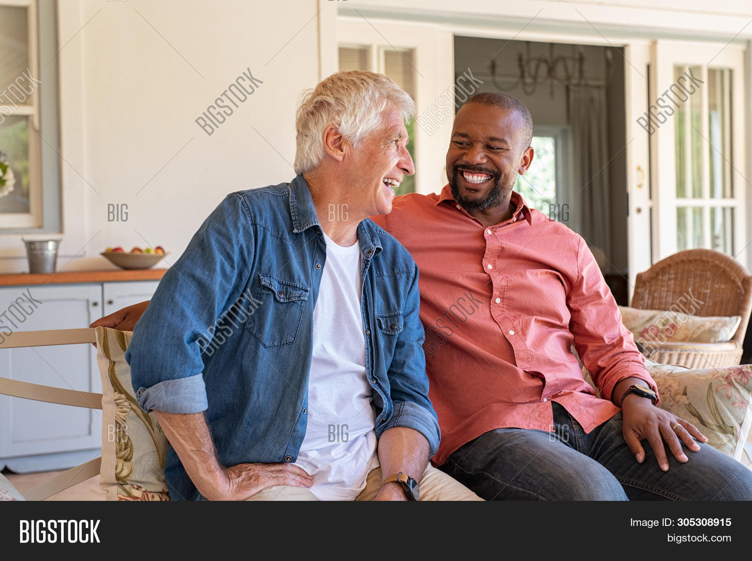 Two friends talking while sitting on couch in the courtyard. Senior man and african guy laughing whi