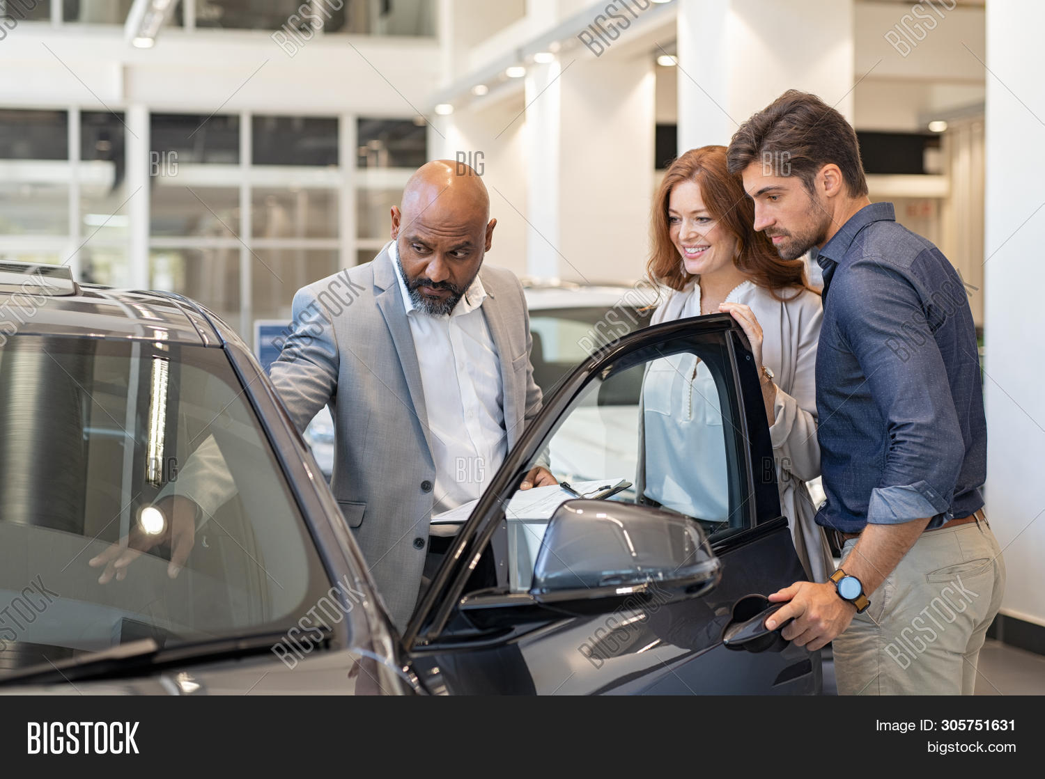 Mature african salesman showing all the car features to young couple. Car dealer showing new car to