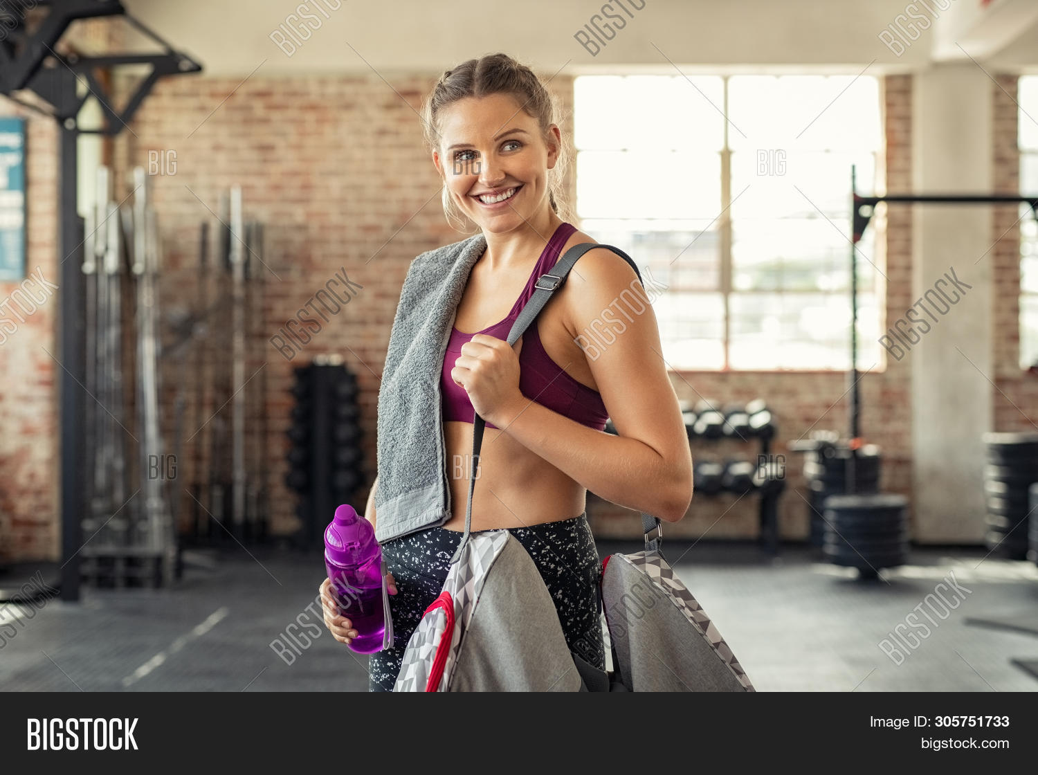 Young smiling woman in sportswear carrying gym bag. Happy fitness girl with sports bag after exercis