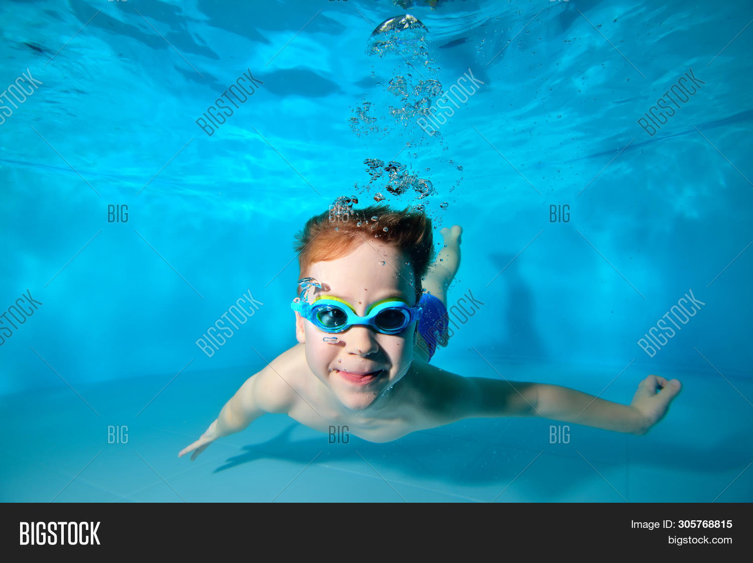 Happy Smiling Baby, Boy, Swimming Underwater In Swimming Pool In Swimming Glasses And Posing For Cam